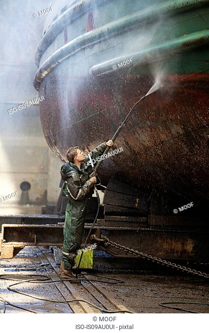 Shipyard worker cleaning boat with high pressure hose