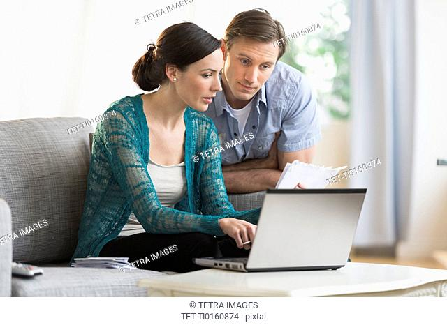 Couple using laptop together to pay bills