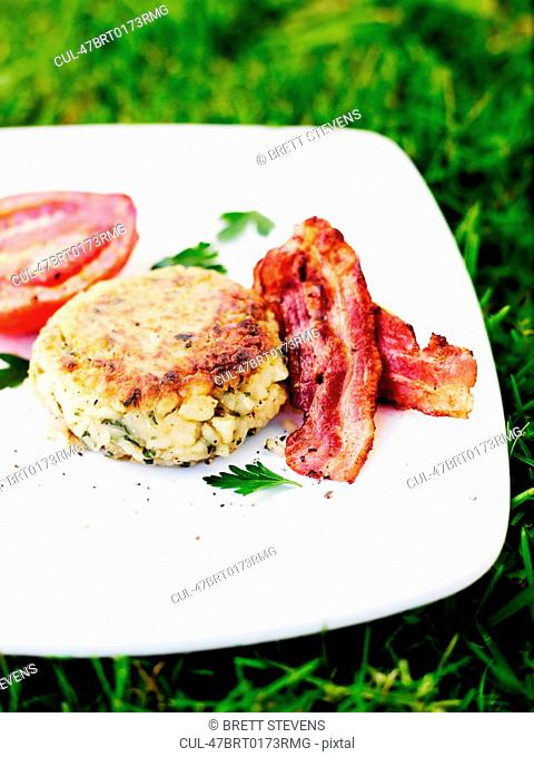 Plate of bacon with biscuit and tomato