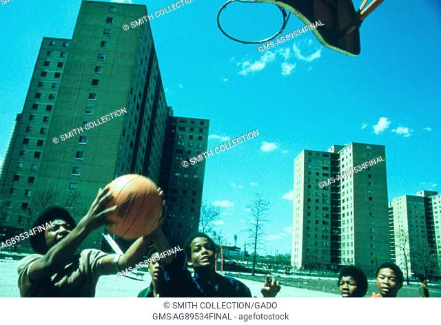 Teen boys wrestle for the basketball during a pick up game outside Stateway Gardens' Highrise Housing Project in the South Side of Chicago, Illinois, 1973