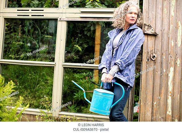 Portrait of mature woman with watering can leaning against greenhouse