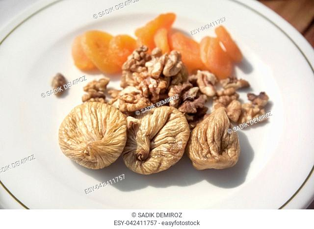 close up shot of dried fruits and walnut plate on breakfast table