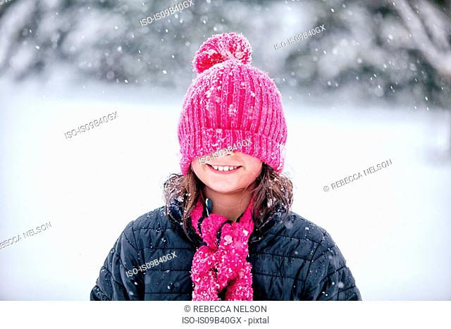 Girl with pink knitted hat pulled over eyes
