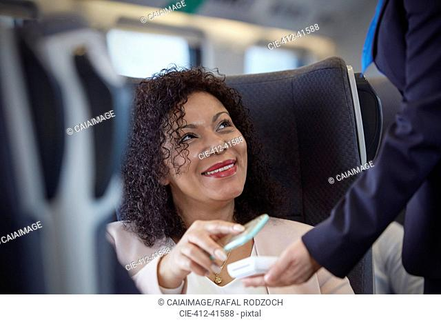 Smiling woman with smart phone using contactless payment on passenger train