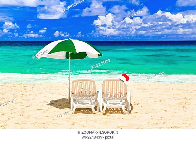 Chairs on tropical beach and Santa Claus red christmas hat