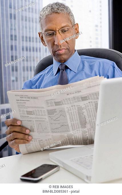 Mixed race businessman reading newspaper at desk