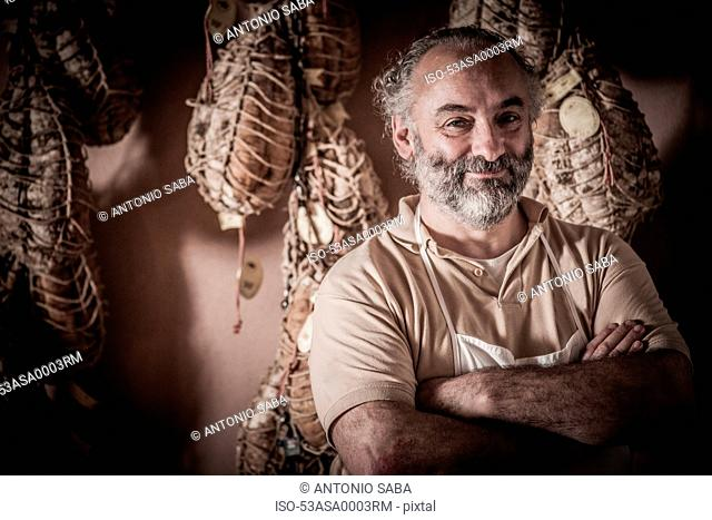 Butcher standing by hanging meat