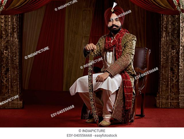 Portrait of a Sikh groom sitting with a sword