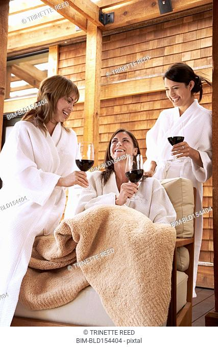 Women drinking red wine in armchairs on spa deck