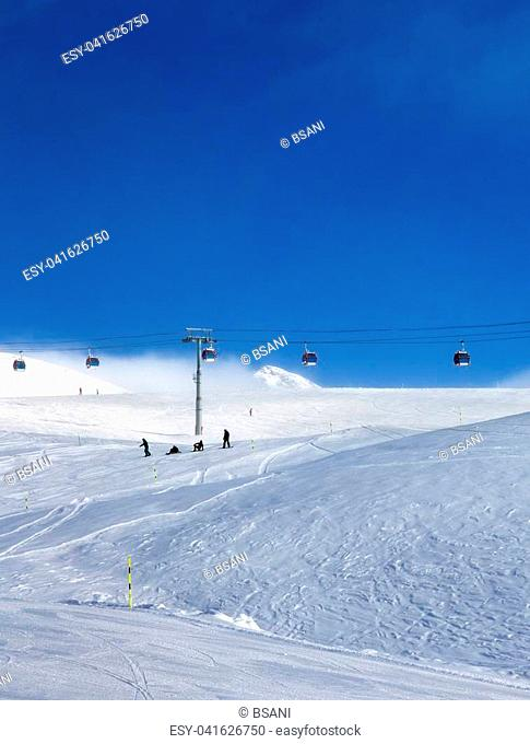 Gondola lift and snowy ski slope in fog at nice sun evening. Caucasus Mountains in winter, Georgia, region Gudauri