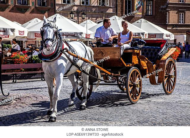 Poland, Mazovia Province, Warsaw. A young woman tourist takes a ride in a horse and carriage in Stary Rynek in Warsaw