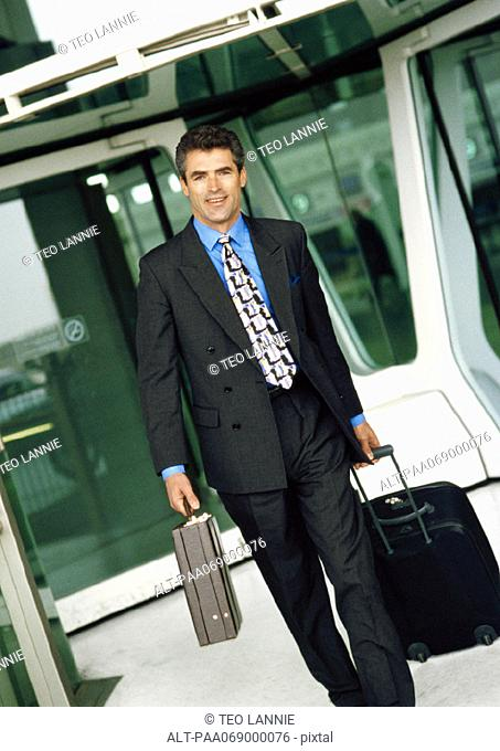 Businessman walking with luggage and briefcase