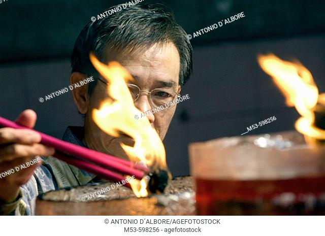 an indonesian man light up incense sticks in Vihara Dharma Bhakti temple in chinatown. west jakarta. indonesia. asia