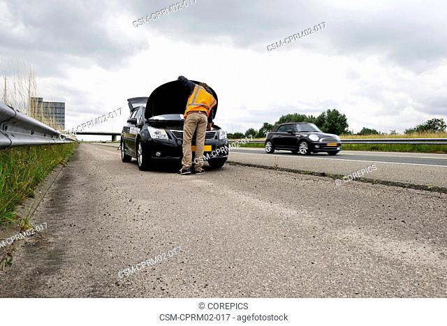 Stranded motorist, trying to fix the engine of his car on the shoulder of a motorway, with traffic passing by