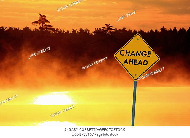 a caution sign beside a lake at sunrise that says CHANGE AHEAD