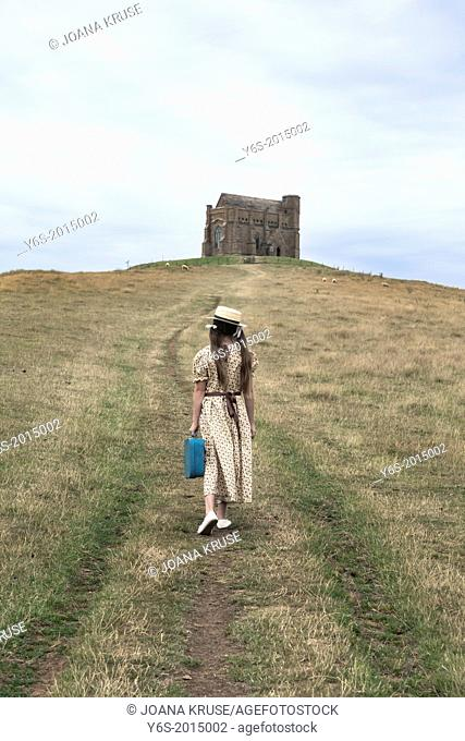 a girl in a vintage dress is walking uphill to a chapel