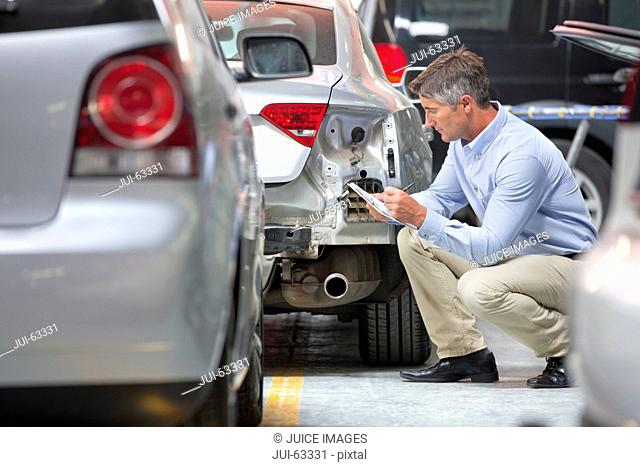 Insurance assessor inspecting damaged vehicle