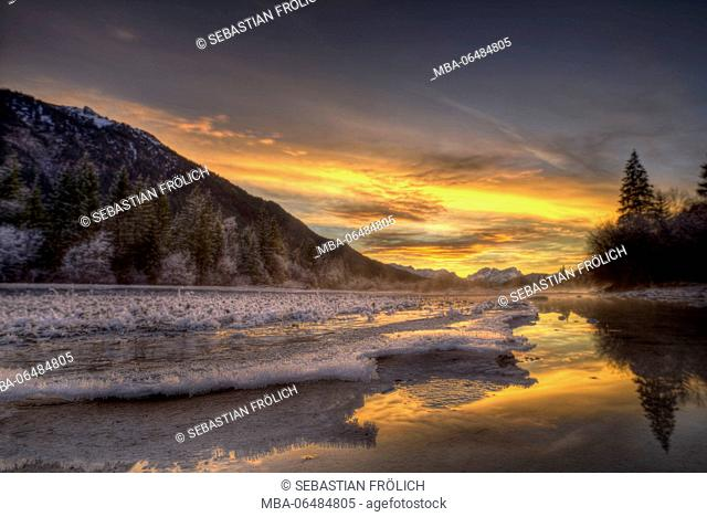Spectacular sundown in the Isar meadows near Wallgau. In the foreground fine ice structures, in the background in distance the Wetterstein Range with Zugspitze