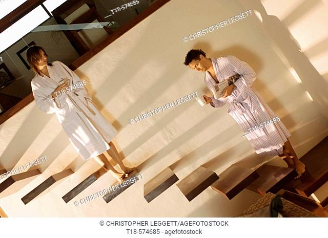 couple in bathrobe standing on stairs holding cups