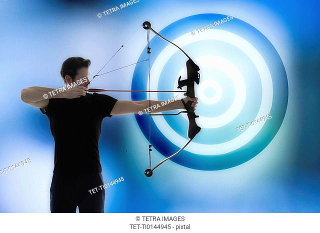 Man holding bow and aiming with blue circle in background