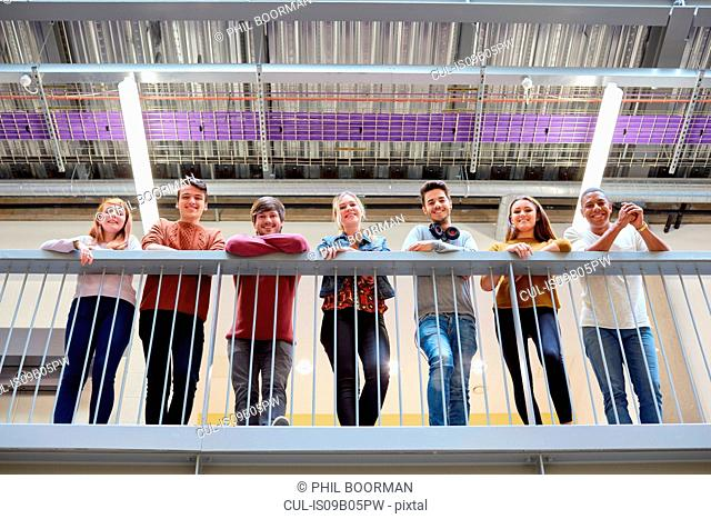 Portrait of male and female students looking down from balcony in higher education college