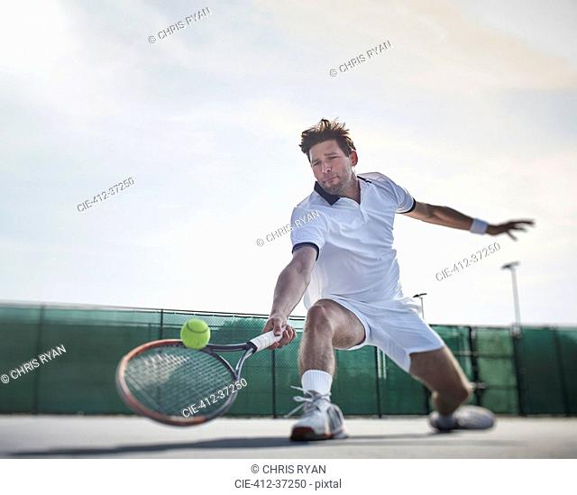 Determined young male tennis player playing tennis, reaching for the ball on sunny tennis court