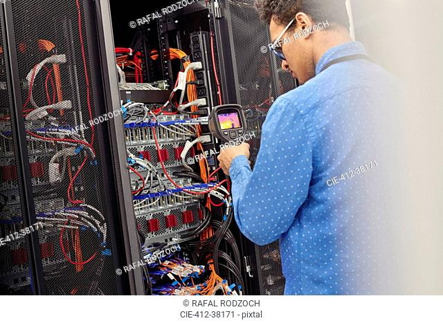 Male IT technician performing diagnostics on panel in server room