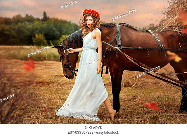 Girl walks into the field with a horse fall. girl long white dress and red wreath on his head