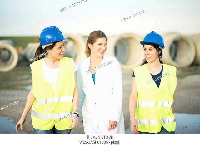 Female colleagues in a factory smiling at each other