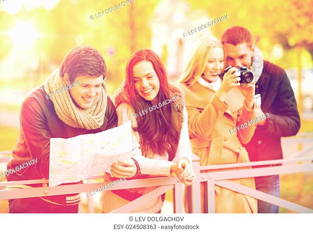 holidays and tourism concept - group of friends or couples with tourist map and camera in autumn park
