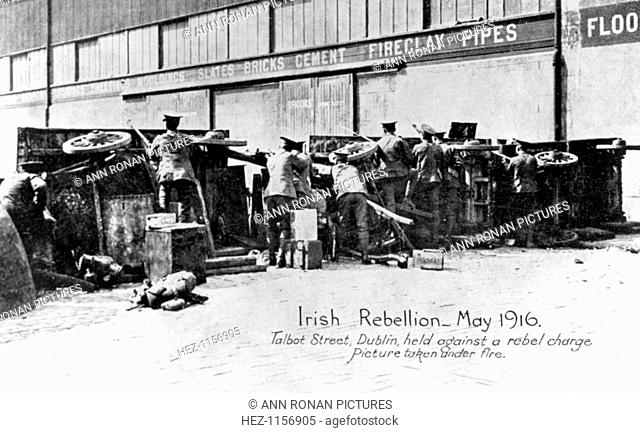 English troops under fire in Talbot Street, Anti-English Irish uprising, Dublin, May 1916. English troops under fire behind a barricade of cars