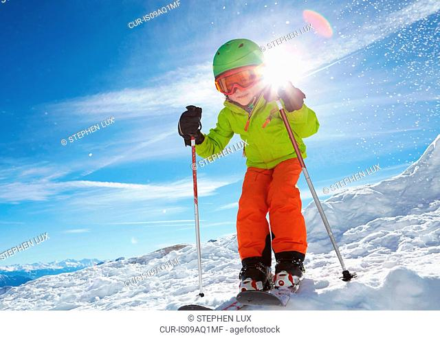 Young boy skiing downhill, low angle view