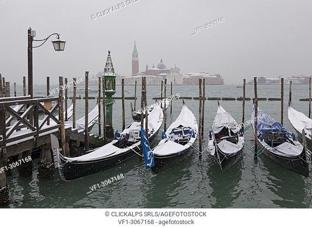 Some traditional venetian gondolas moored at Riva degli Schiavoni during a snowfall, Venice, Veneto, Italy