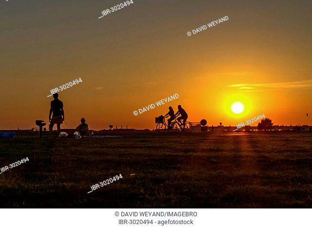 Couple having a barbecue on Tempelhof Airfield in the evening sun in front of two passing cyclists