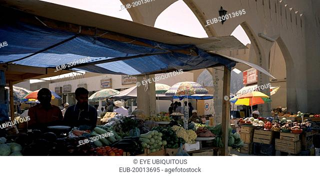 Mutrah produce market. Covered stalls beside arched entrance with displays of fruit and vegetables