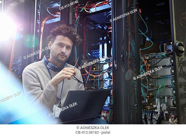 Portrait confident male IT technician working at laptop in server room