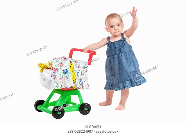 Little girl in denim dress with hand raised up carries a shopping cart full baby clothes isolated on a white background