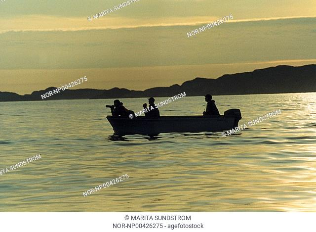 Silhouette of a boat with people at evening