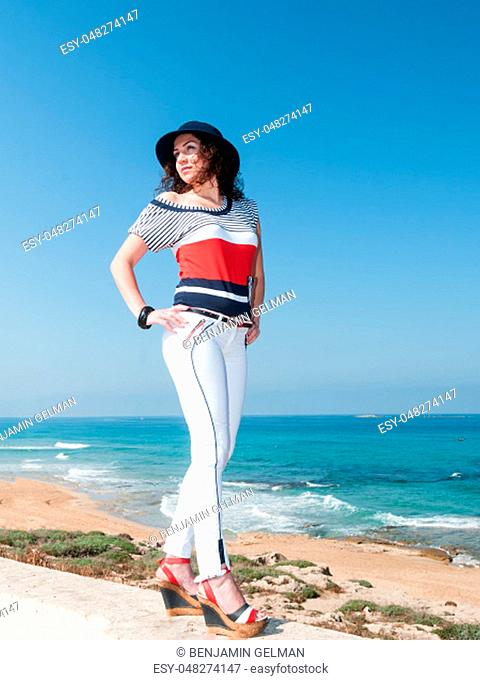 Portrait of a laughing girl in white jisa and blue hat against the blue sea on a warm summer day