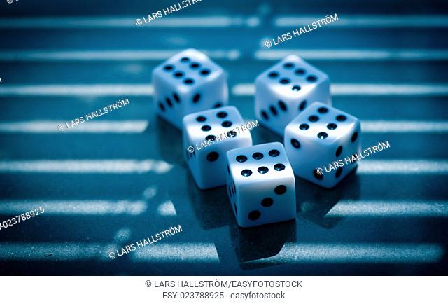 Dice on stone surface at night. All sixes. Concept of risk, chance and mystery