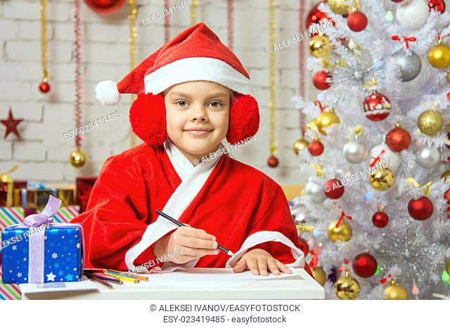 Six year old girl dressed in a red suit Santa Claus draws pencils are in a festive Christmas interior