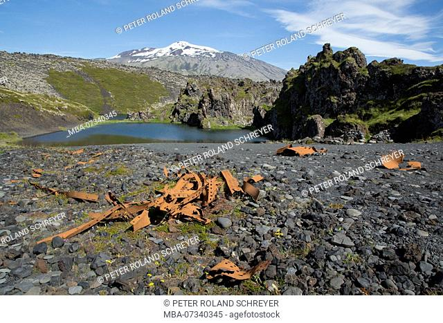 Iceland, beach with wreckage at Dritvik, small lake, Snaefellsjökull, red rocks