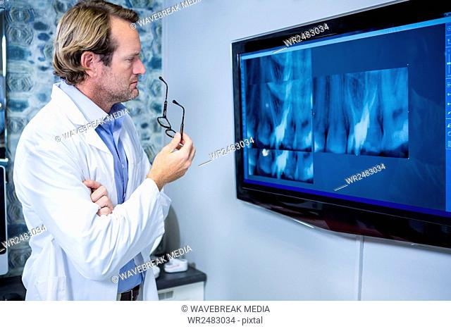 Thoughtful dentist examining an x-ray on the monitor