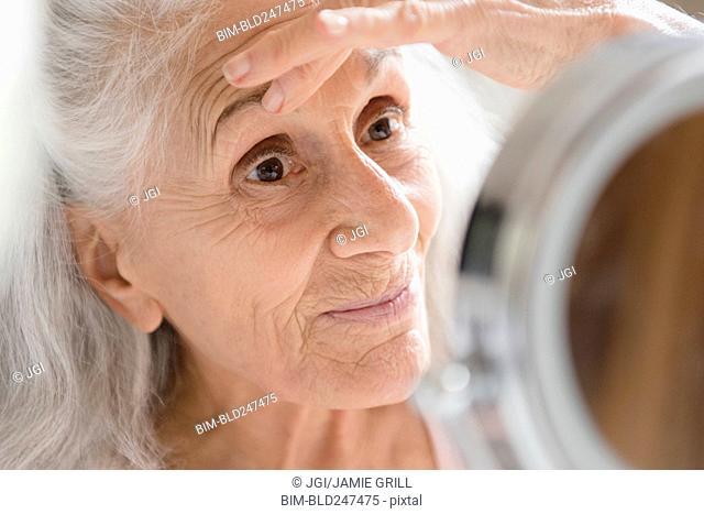 Older woman checking eye wrinkles in mirror