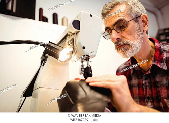 Low angle view of cobbler using the sewing machine