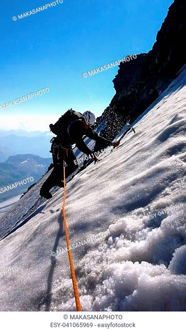 A vertical view of a mountain guide on a steep and exposed glacier in the Swiss Alps