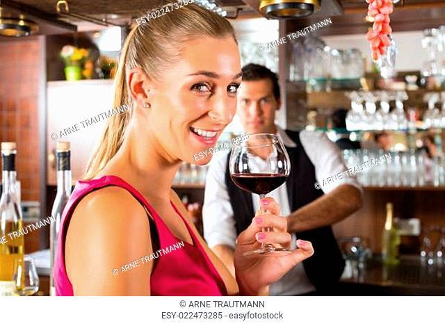 Frau hält ein Glas Wein in der Hand an der Bar