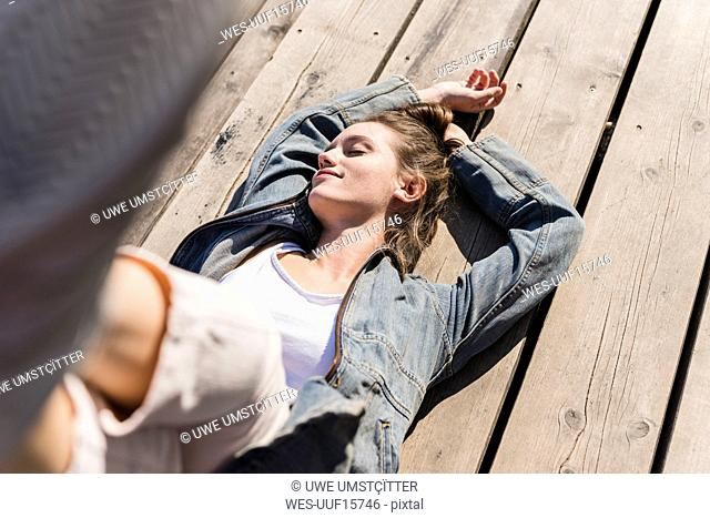 Relaxed young woman lying on wooden boards in sunshine