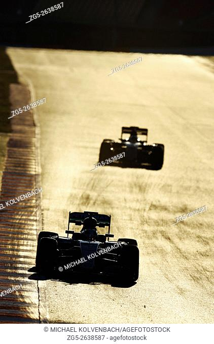 Two Formula One cars race down a straight during testing sessions on the Circuit de Barcelona-Catalunya racetrack, Spain