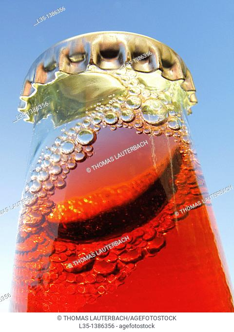 Shaken bottle neck with crown cap and a red liquid and many bubbles